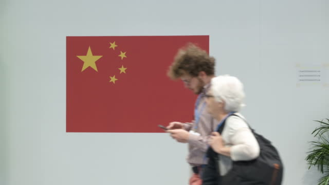 a man tholding a mobile phone walks past a chinese flag at the china pavilion at the unfccc cop25 climate conference on december 3 2019 in madrid... - fifa world cup 2010 stock videos & royalty-free footage