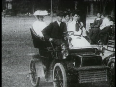 b/w 1904 man + three women in car stop at porch + get out / man gets back in + drives off - 1900~1909年点の映像素材/bロール