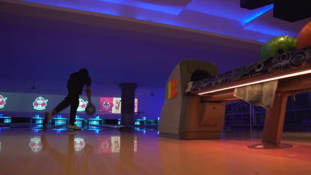 vídeos de stock, filmes e b-roll de homem jogando uma bola de boliche em uma pista de boliche - sapato de boliche