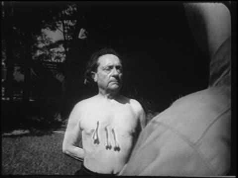 vídeos y material grabado en eventos de stock de b/w 1951 man throwing darts into chest of shirtless man / newsreel - 1951