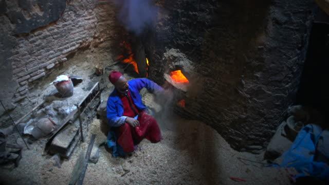 vídeos y material grabado en eventos de stock de man throwing sawdust into fire - balneario