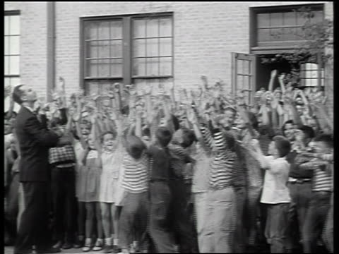 b/w 1947 man throws packs of bubble gum to crowd of children outside of school / newsreel - 1947年点の映像素材/bロール