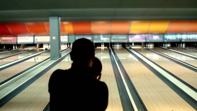 man  throws up ball on skittles in bowling club - bowl stock videos & royalty-free footage