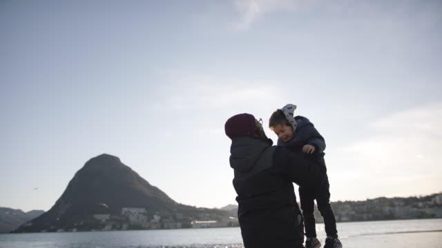 stockvideo's en b-roll-footage met de mens werpt jonge jongen in de lucht, allebei het glimlachen - zoon