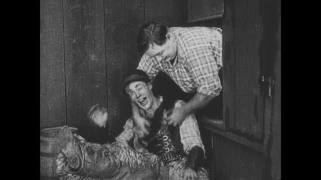 vídeos de stock e filmes b-roll de 1918 man (fatty arbuckle) tickles wild bill hiccup to help the salvation army woman escape - bandido