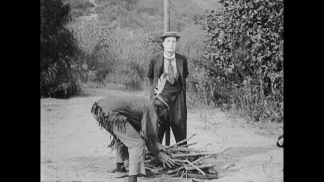 vídeos de stock e filmes b-roll de 1922 man (buster keaton) tied to stake keeps moving stake - dança da guerra