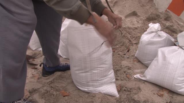 a man ties a knot on a sandbag - sandbag stock videos & royalty-free footage