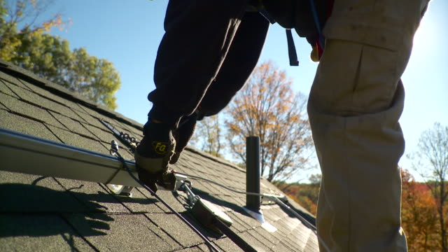 ms tu man tightening down bolt to rail on the roof for solar panels - solo uomini giovani video stock e b–roll