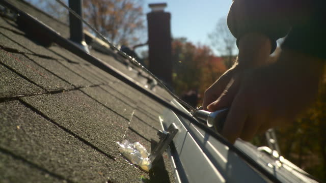 cu man tightening down bolt to rail on the roof for solar panels - solo uomini giovani video stock e b–roll
