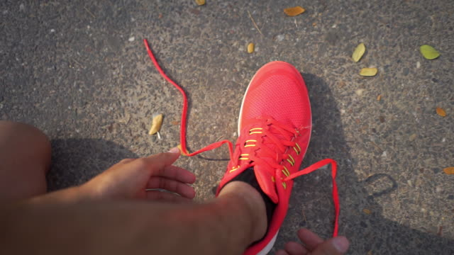 man tightening the knot lace sports shoe, rady for workout and run in the morning - personal perspective stock videos & royalty-free footage