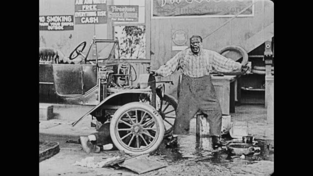 1920 man (buster keaton attempts) to fix a car and sprays oil in man's (fatty arbuckle) face - slapstick stock videos & royalty-free footage