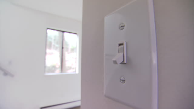 a man toggles a light switch on and off again. - light switch stock videos & royalty-free footage