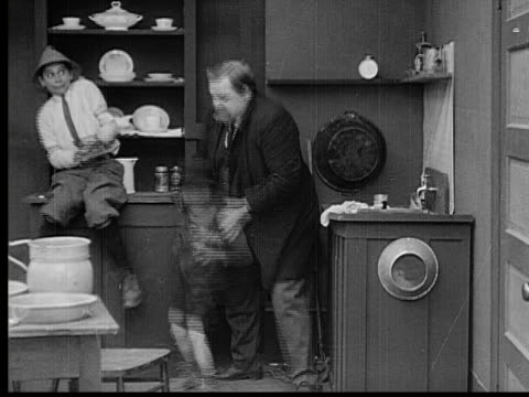 1913 b/w montage ms man (fatty arbuckle) tosses boys out of house, throws plates and chairs at them, and falls down / usa - コメディアン点の映像素材/bロール