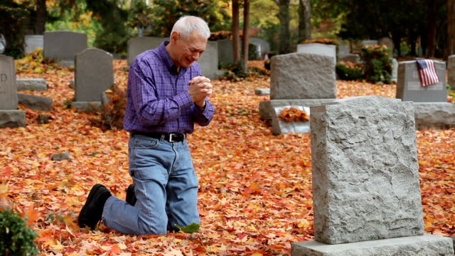 man totally upset crying, and grieving at grave in cemetery - kneeling stock videos and b-roll footage