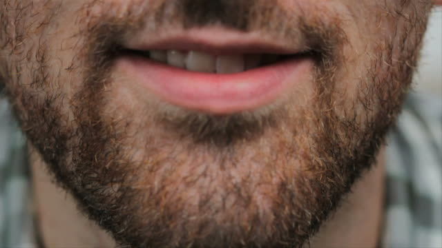A man touches his beard. Extreme closeup.