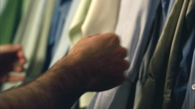 vídeos y material grabado en eventos de stock de cu pan man touching button-down shirts in closet and selecting long-sleeved white shirt / new york - camisa blanca