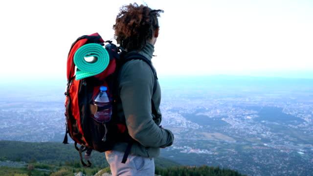Touristique d'homme debout sur le sommet de la montagne et souriant à la caméra.