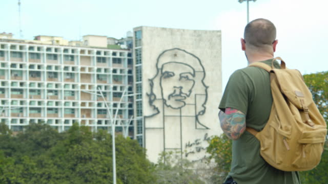 man tourist with tattoo and backpack looking at che guevara monument at havana plaza de la revolucion - government stock videos & royalty-free footage