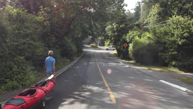 Man låter flytta ocean kajak längs landsbygden street