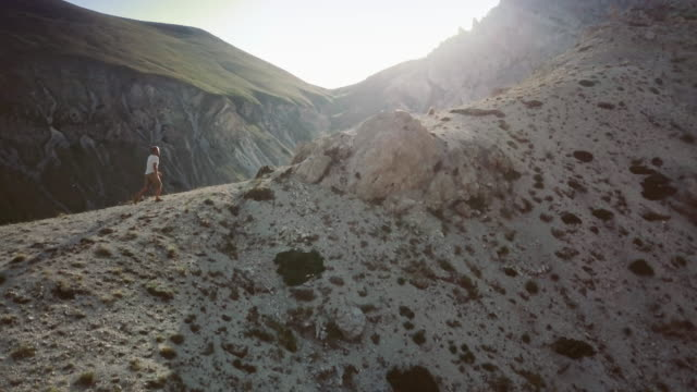 Man trail hiking on high mountain: drone aerial view