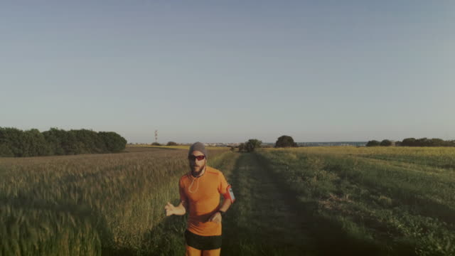 Man trail running in a field: drone aerial view
