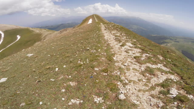 Man trail running on a dangerous ridge POV