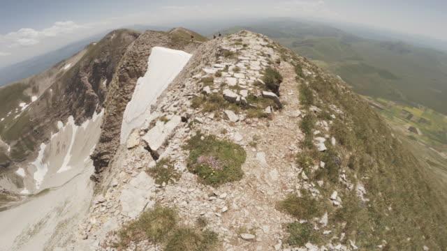 vídeos de stock e filmes b-roll de man trail running on a dangerous ridge pov - filme de ação