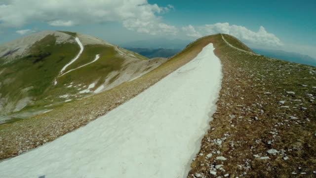 Man trail running on a dangerous ridge with snow POV