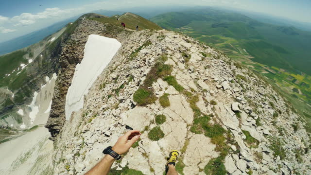 man trail running on a exposed cliff pov - rock face stock videos and b-roll footage