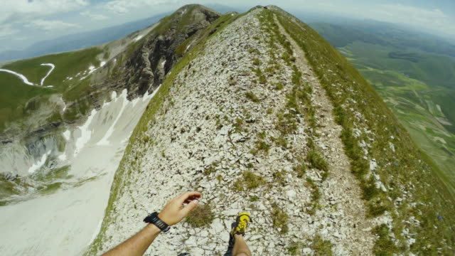 Man trail running on a exposed cliff POV