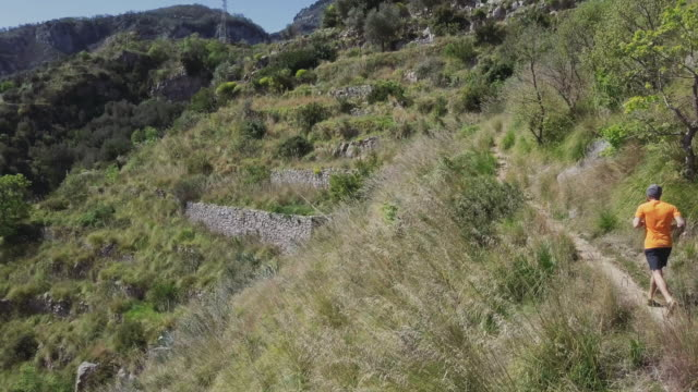 man trail running on a single track on high cliff: drone aerial view - named wilderness area stock videos & royalty-free footage
