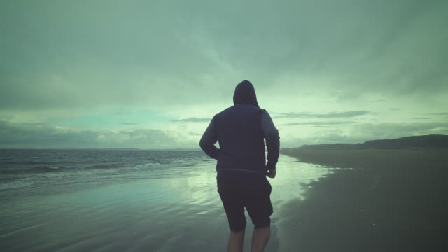 vídeos de stock, filmes e b-roll de man training at beach. - calções de corrida