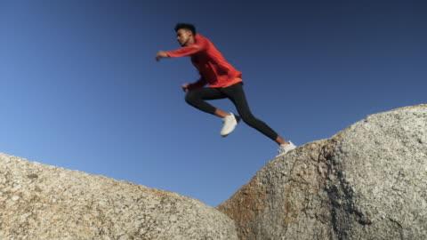man training on beach rocks, low angle - sports training 個影片檔及 b 捲影像