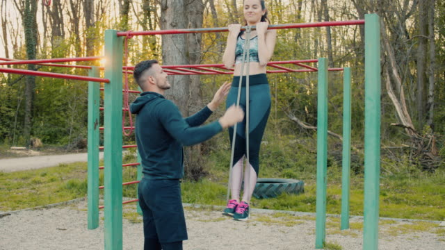 slo mo ms man training woman outdoors - pull ups stock videos & royalty-free footage
