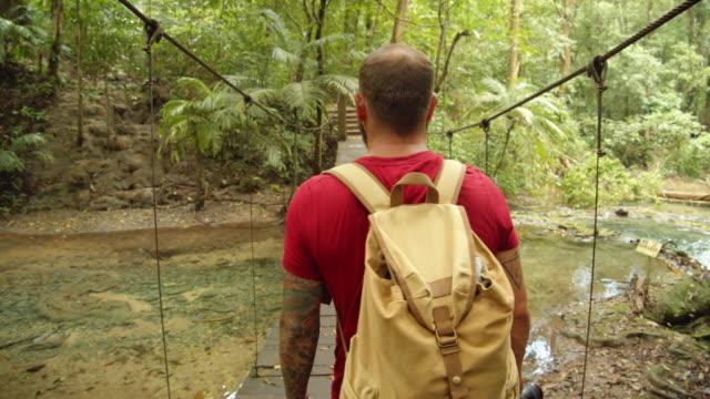 vídeos de stock e filmes b-roll de man traveler walking along a suspension wooden bridge at palenque mayan ruins, mexico - atividade recreativa