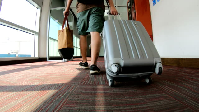 Man Traveler with Luggage Walking Through Airport Terminal