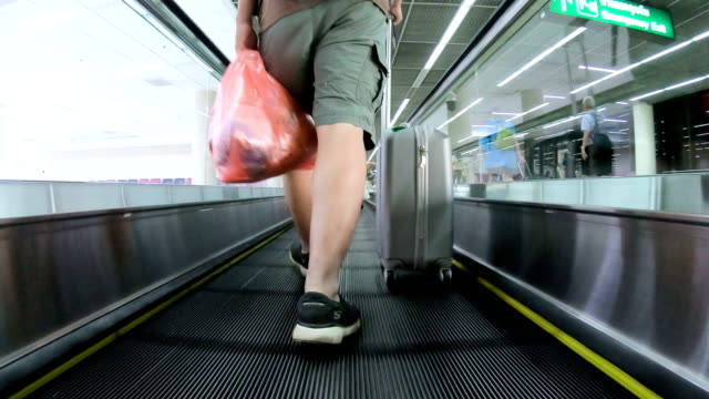 man traveler with luggage walking through airport terminal - wheeled luggage stock videos and b-roll footage