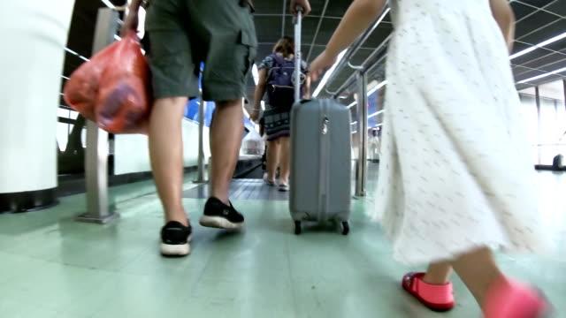 Man Traveler with Luggage Walking Through Airport Terminal