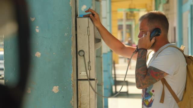 man traveler with tattoos using public phone at havana cuba - telefonzelle stock-videos und b-roll-filmmaterial
