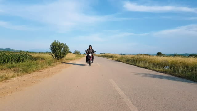 uomo in viaggio in moto su strada - motor video stock e b–roll