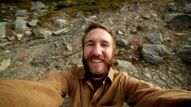 Man traveling taking selfie portrait on mountain trail