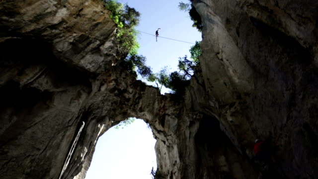 Man traverses highline stretched above deep canyon,gorge