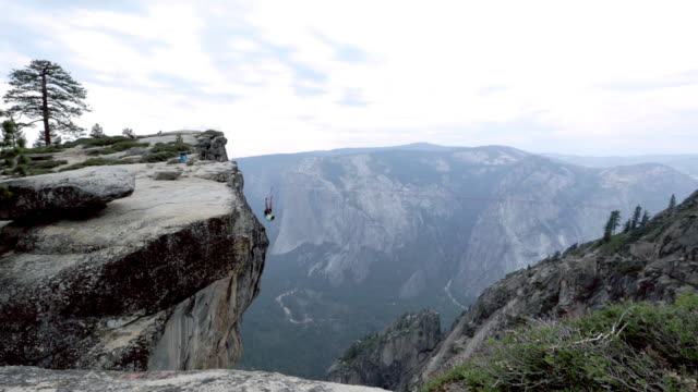 Man traverses highline stretched above deep valley