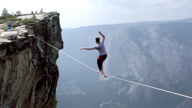 vidéos et rushes de man traverses highline stretched above deep valley - danger