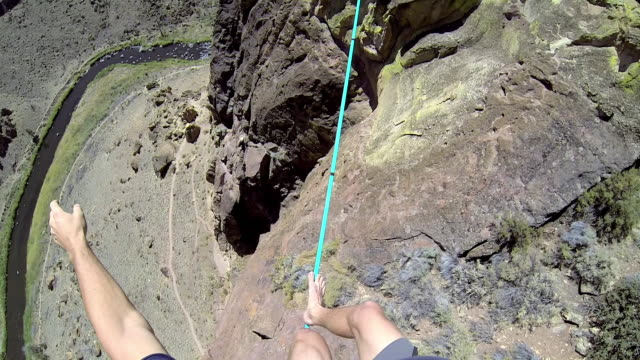 Man traverses highline stretched above desert valley