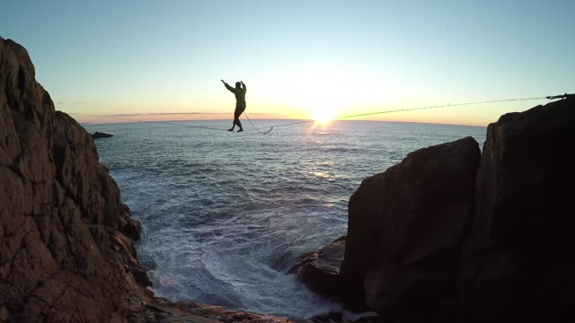 man traverses highline stretched above sea below - courage stock videos & royalty-free footage
