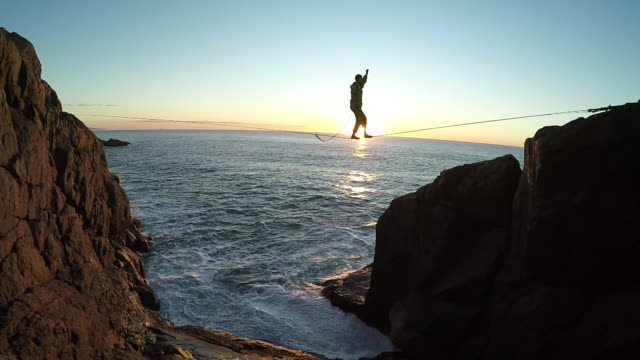 Man traverses highline stretched above sea below