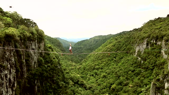 man traverses highline stretched above valley, waterfall - risk stock videos & royalty-free footage