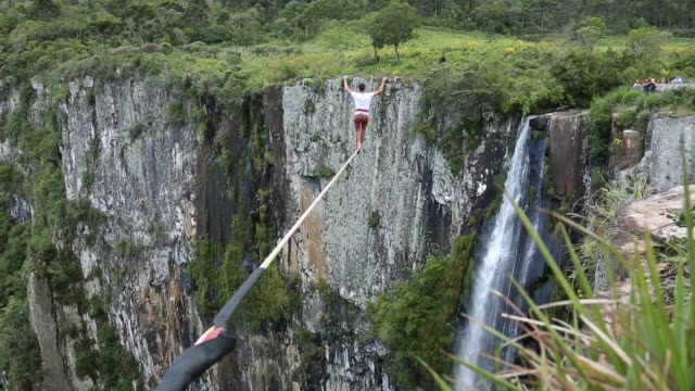 Man traverses highline stretched above valley, waterfall