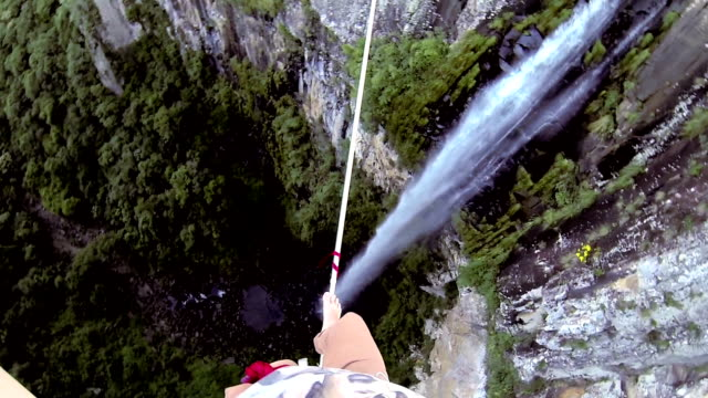 man traverses highline stretched above waterfall, valley - anticipation stock videos and b-roll footage